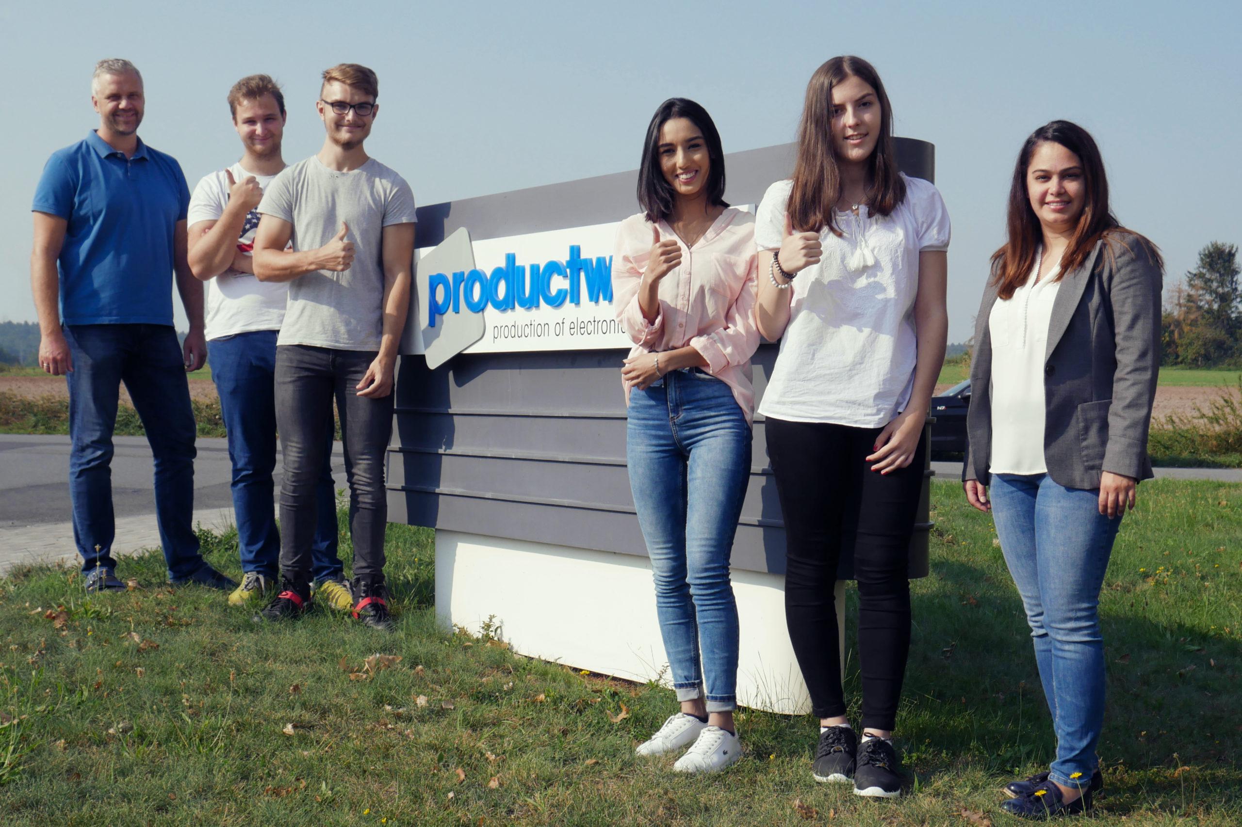 Auszubildende vor dem Firmenschild der productware GmbH
